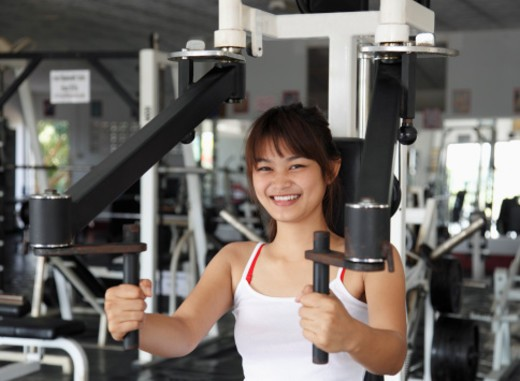 Stock Photo: 1598R-10076349 Young woman smiling on chest machine