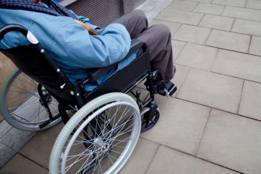 Stock Photo: 1598R-10076371 Elderly man sitting in wheelchair and holding walking cane.