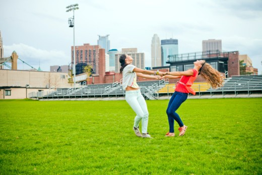 Stock Photo: 1598R-10076498 Two girlfriends having fun together outside in a urban park.