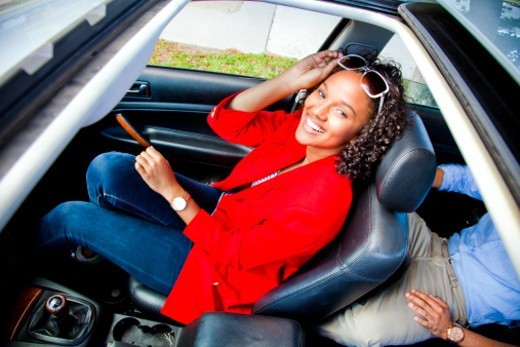 Stock Photo: 1598R-10077459 A teenage female sitting in the passenger seat of a automobile smiling and having fun.
