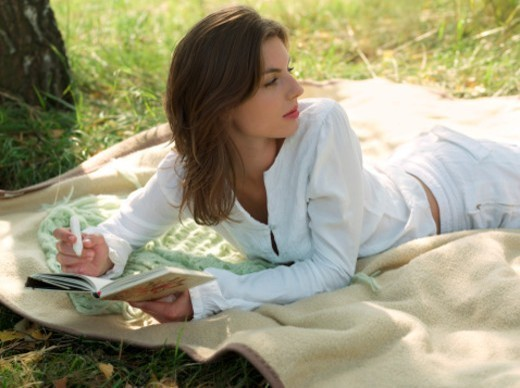 Stock Photo: 1598R-10077740 Young woman writing in diary on blanket outdoors