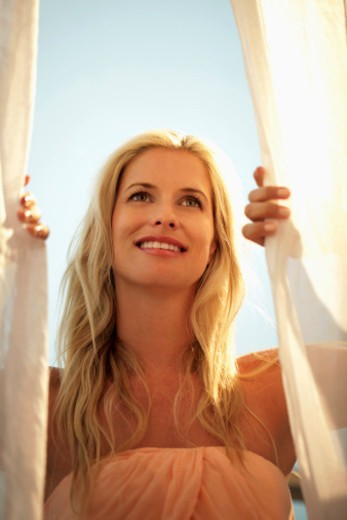 blond woman looking out of window : Stock Photo