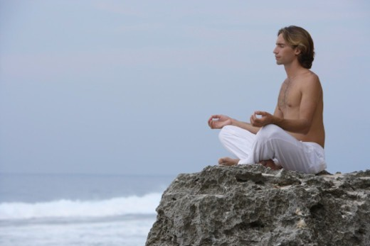 man practicing yoga on rocks : Stock Photo