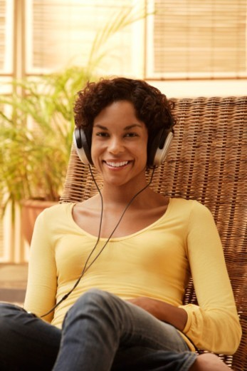 Stock Photo: 1598R-10079098 Young woman listening to music and smiling.