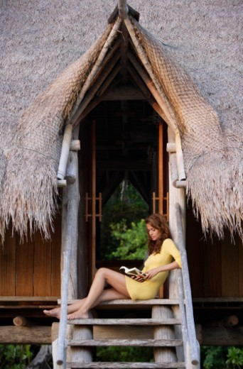 woman reading on steps of tropical home : Stock Photo