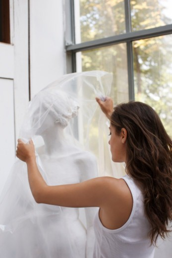 Stock Photo: 1598R-10079756 artist unwrapping sculpture