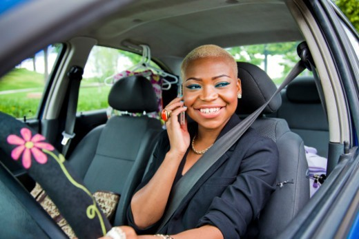 Stock Photo: 1598R-10079830 A young female using a cellular device in the drivers seat of her car.
