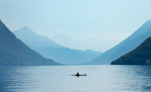 Lone rower in the middle of a lake : Stock Photo