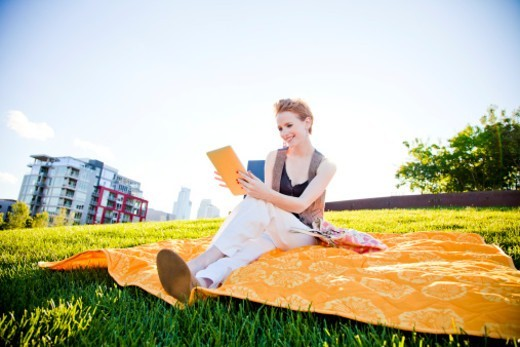 Stock Photo: 1598R-10080302 A teenage girl using a tablet deice and smiling outside in a park.