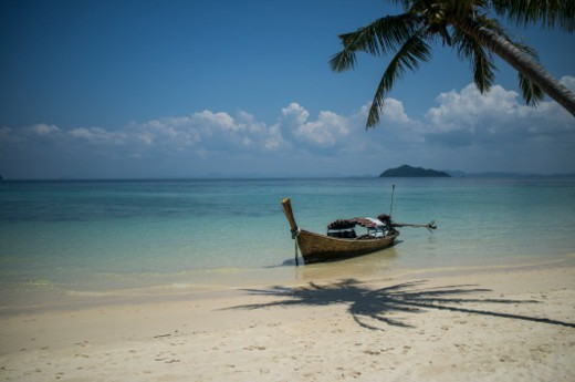 A long boat anchored off the beach under palm tree in southern Thailand : Stock Photo