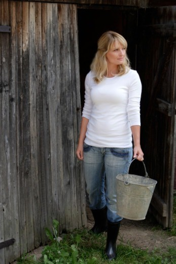 Stock Photo: 1598R-10080734 woman walking out of barn
