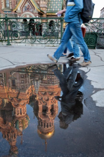 Stock Photo: 1598R-10081766 tourists walking past a puddle with the  Church on Spilled Blood reflected in it