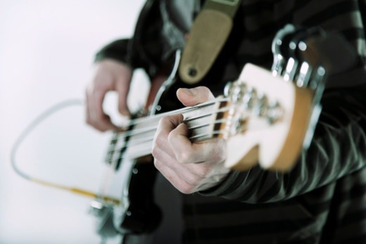 hands of the musician playing his guitar : Stock Photo