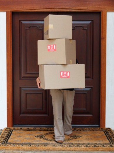 Person carrying 3 packages outside of front door : Stock Photo