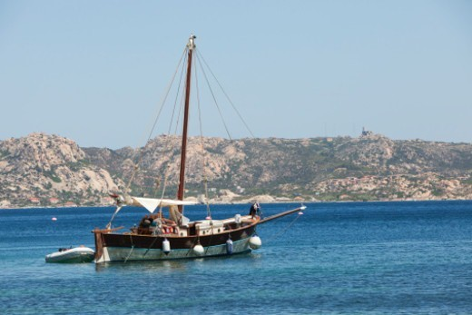 Stock Photo: 1598R-10082785 Wooden yacht anchored in blue sea paradise. Holiday makers are relaxing on the deck under the canopy which provides some shade from the sun. The scenery is the Archipelago di la Maddalena, a marine park north of Sardinia
