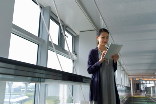 Stock Photo: 1598R-10083110 Business woman using a tablet PC at an airport