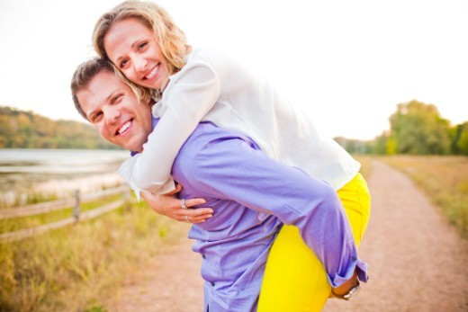 A young and happy couple smiling and having fun together outside in a park. : Stock Photo