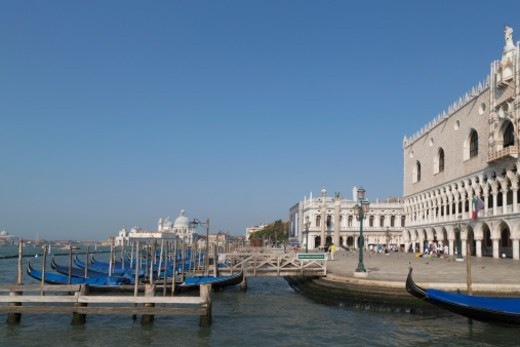 a line of gondolas moored in front of the Doges Palace with Santa Maria della Salute in the distance : Stock Photo