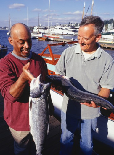 Stock Photo: 1598R-101402 Two fishermen at pier holding catch