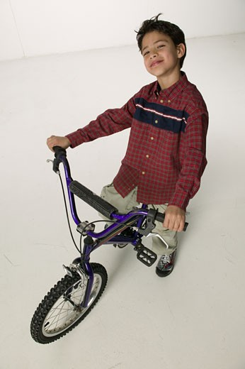 Boy (8-9) sitting on bicycle in studio, elevated view : Stock Photo