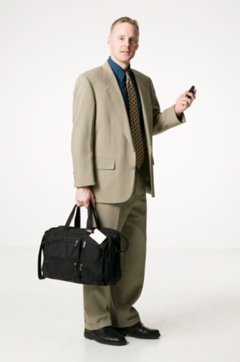 Stock Photo: 1598R-101986 Businessman holding bag and mobile phone, posing in studio, portrait