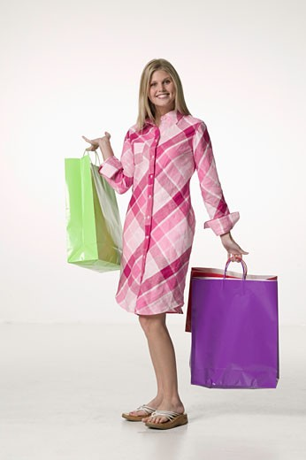 Young woman holding shopping bags, posing in studio, portrait : Stock Photo