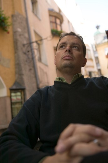 Man sitting outside in old historical city, admiring view, low angle view : Stock Photo