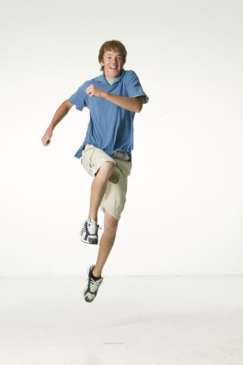 Teenage boy (16-17) jogging mid-air : Stock Photo