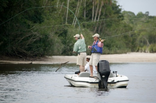 Two men on motorboat, fishing : Stock Photo