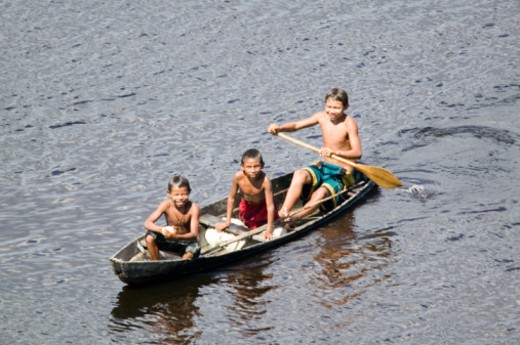 Stock Photo: 1598R-102832 Three boys (6-7), (10-11) paddling canoe, portrait, elevated view