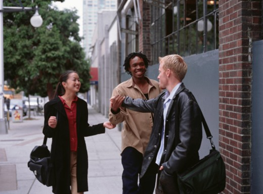 Three friends smiling, standing on city sidewalk : Stock Photo