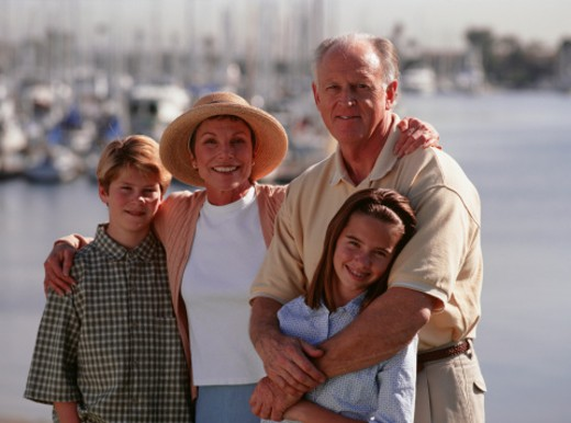 Family standing on pier, boats in background, portrait : Stock Photo