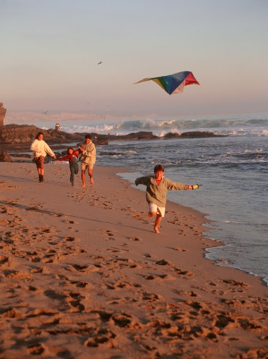 Stock Photo: 1598R-103057 Family with two children  (6-7), (8-9), flying kite on beach