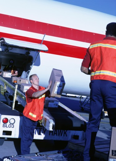 Stock Photo: 1598R-103140 Baggage personnel loading aeroplane at airport