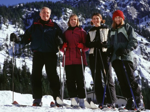 Parents with two daughters skiing in mountains, portrait : Stock Photo