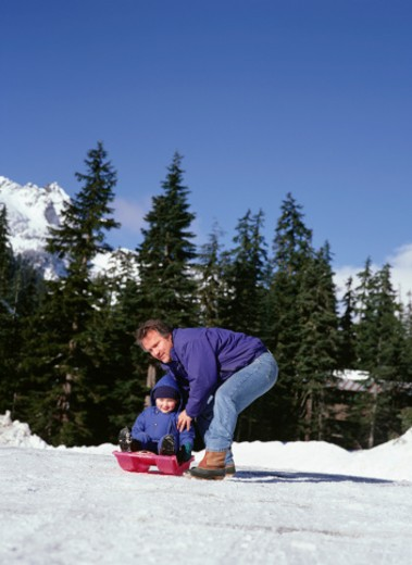 Father and son (4-5), sledging in mountains : Stock Photo