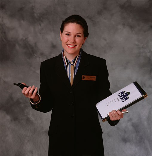 Woman representative holding notebook and mobile phone in studio, portrait : Stock Photo