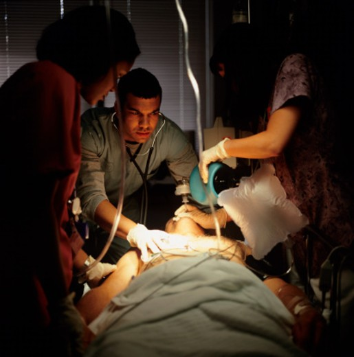 Medical staff resuscitating man in hospital : Stock Photo