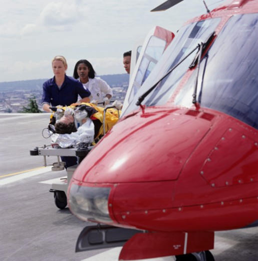 Medical staff moving patient on bed from rescue helicopter : Stock Photo