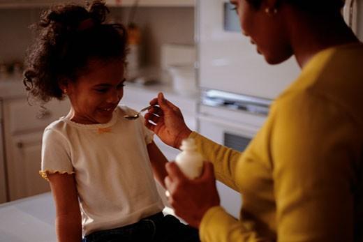 Stock Photo: 1598R-103385 Young girl (4-5) refusing to take teaspoon of medicine