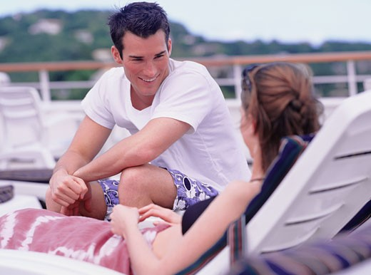Stock Photo: 1598R-103490 Young couple on deckchairs, on cruise ship deck