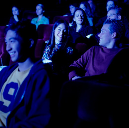 Group of people laughing at film in cinema : Stock Photo