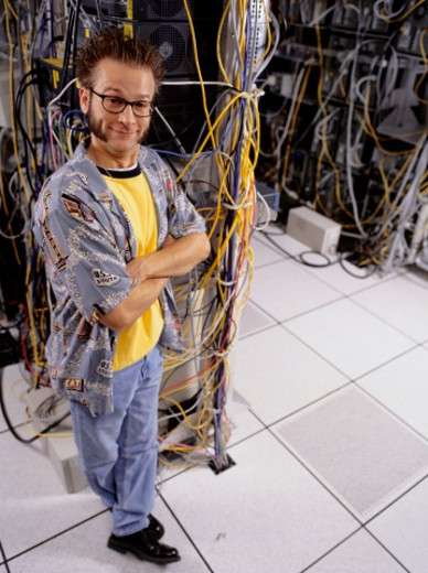 Man standing by cables in computer room : Stock Photo