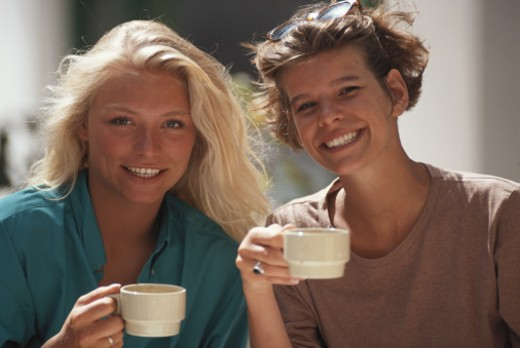 Two women holding cup, smiling, close-up : Stock Photo