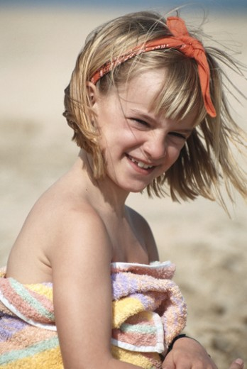 Girl (4-5) wrapped in towel on beach, smiling : Stock Photo