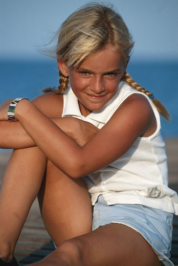 Girl (8-11) sitting on jetty, smiling, portrait : Stock Photo
