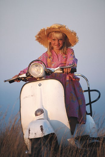Girl (6-7) with on scooter in field, smiling : Stock Photo