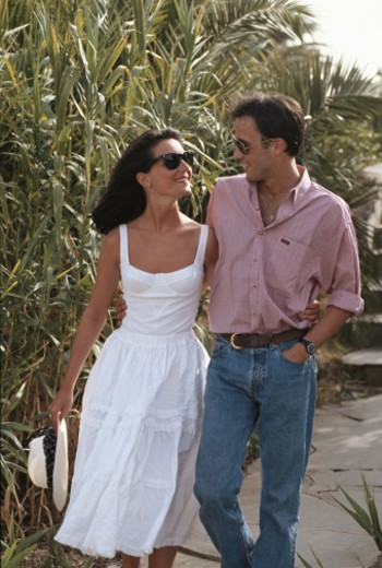 Couple walking outdoors, smiling, face to face : Stock Photo