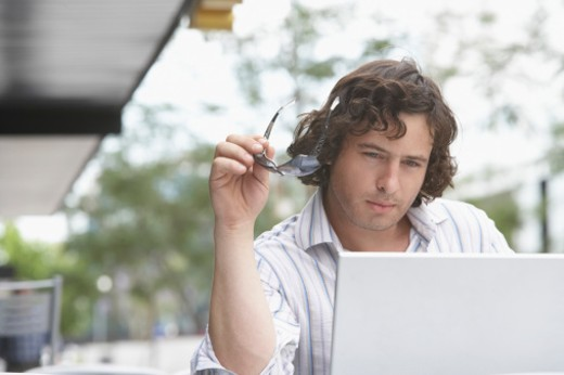 Businessman holding sunglasses and looking at a laptop : Stock Photo