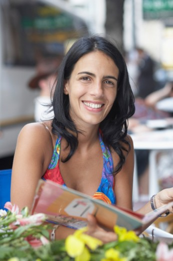 Stock Photo: 1598R-104842 Portrait of a young woman holding a menu card and smiling